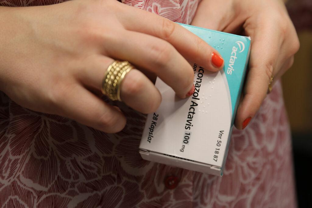 Bild på en person som läser punktskrift på en läkemedelsförpackning.